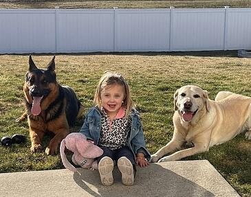 MSA canine Carter, retired canine York, posing with Bradley's 3 year old daughter